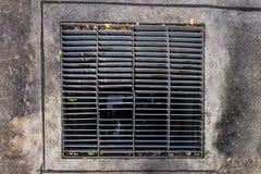 Alcantarilla rectangular con un moho y agujeros Imagenes de archivo