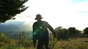 Alcanzar la tapa El salto del hombre feliz y aumentar para arriba las manos en lanscape hermoso de la montaña en salida del sol F almacen de video