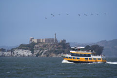 Alcatraz Ferry. Bright yellow ferry boat heading to Alcatraz island against blue sky with birds. Horizontal Format Royalty Free Stock Photography