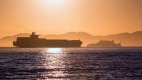 Alcatraz-Inselgefängnis am Sonnenuntergang und am Handelsschiff Lizenzfreies Stockfoto