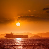 Alcatraz island penitentiary at sunset and merchant ship Stock Photo