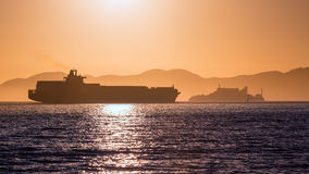Alcatraz island penitentiary at sunset and merchant ship Royalty Free Stock Photo