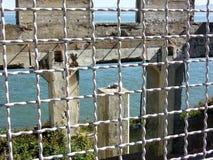 Alcatraz San Francisco - fördärvar av en gammal byggnad till och med ett staket royaltyfri bild