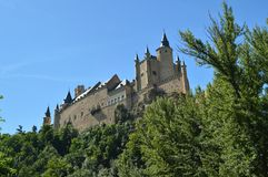 Alcazar Castle Seen From The River That Runs Through The Valley That Reigns In Segovia Slightly Caught By A Small Grove. Architect stock photo