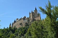Alcazarslotten som sågs från floden, som kör till och med dalen, som härskar i Segovia, fångade litet vid en liten dunge _ arkivfoto