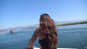 Alce la opinión trasera la chica joven que se sienta en el arco del barco y que mira al paisaje hermoso de la naturaleza durante  almacen de metraje de vídeo