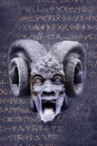 Alchemical Devil. Screaming goat-horned devil against a background of mysterious alchemy symbols royalty free stock photography