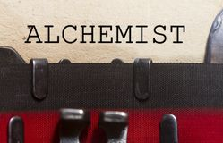 Alchemist typed on a vintage paper. Alchemist as  typed on an old vintage paper with od typewriter font Royalty Free Stock Image