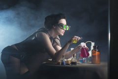 Alchemist girl. With test tubes in hand on a gray background Stock Image