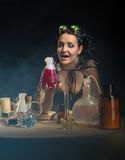 Alchemist girl with test tubes. Beautiful alchemist girl with test tubes on gray background Stock Images