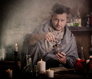 Alchemist at the table Royalty Free Stock Images
