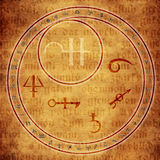 Alchemy. Circle with astrological and alchemy symbols over medieval text Royalty Free Stock Photo