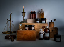Alchemy lab. bottles, jars, scales, candle on wooden shelves Stock Images