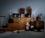 Alchemy lab. bottles, jars, scales, a kerosene lamp on wooden shelves Stock Photos