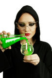 Alchemy poisoner. Add green poison into glass of drink isolated over white background Stock Photo