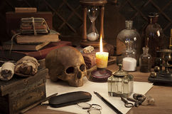 Alchemy still life. With skull and burning candle Royalty Free Stock Photos