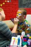 Alchevsk, Ουκρανία - 3 Αυγούστου 2017: Ένα παιδί σύρει ένα πρόσωπο για ένα κόμμα παιδιών ` s Aqua makeup για τα κορίτσια και τα α Στοκ εικόνα με δικαίωμα ελεύθερης χρήσης