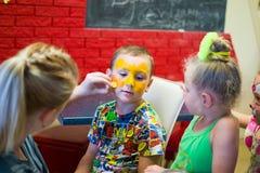 Alchevsk, Ουκρανία - 3 Αυγούστου 2017: Ένα παιδί σύρει ένα πρόσωπο για ένα κόμμα παιδιών ` s Aqua makeup για τα κορίτσια και τα α Στοκ Φωτογραφία