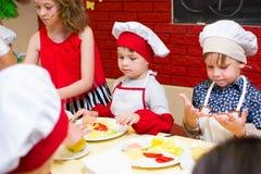 Alchevsk, Ουκρανία - 16 Ιουλίου 2017: Κύρια κατηγορία παιδιών ` s στο μαγείρεμα των πατατών στο φούρνο με το ζαμπόν και το τυρί Στοκ Φωτογραφία