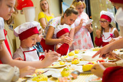 Alchevsk, Ουκρανία - 16 Ιουλίου 2017: Κύρια κατηγορία παιδιών ` s στο μαγείρεμα των πατατών στο φούρνο με το ζαμπόν και το τυρί Στοκ Εικόνες