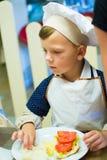 Alchevsk, Ουκρανία - 17 Σεπτεμβρίου 2017: Σχολικός μάγειρας για τα παιδιά να προετοιμαστεί πιτσών Στοκ Φωτογραφία