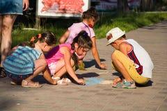 Alchevsk, Украина - 27-ое июля 2017: Дети красят пристань на асфальте Партия ` s детей Стоковые Изображения