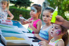 Alchevsk, Украина - 27-ое июля 2017: Дети красят с клеем и покрашенным песком Партия ` s детей Стоковая Фотография RF