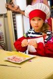 Alchevsk, Украина - 30-ое июля 2017: Кашевары школы для детей Выучите сварить макаронные изделия с сосисками Стоковое Изображение