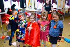 Alchevsk, Украина - 11-ое марта 2018: дети с покрашенными сторонами играют с аниматорами в костюмах Стоковое Изображение
