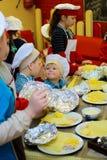 Alchevsk, de Oekraïne - Januari 21, 2018: De kinderen in de vorm van koks leren hoe te om lasagna's te koken stock afbeeldingen