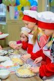 Alchevsk, de Oekraïne - Januari 21, 2018: De kinderen in de vorm van koks leren hoe te om lasagna's te koken royalty-vrije stock afbeelding