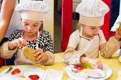 Alchevsk, de Oekraïne - Juli 16, 2017: Kinderen` s hoofdklasse bij het koken van aardappels in de oven met ham en kaas Royalty-vrije Stock Foto