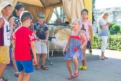 Alchevsk, Ucrânia - 27 de julho de 2017: Jogo de crianças feliz com os animadores no verão Imagem de Stock