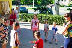 Alchevsk, Ucrânia - 27 de julho de 2017: Jogo de crianças feliz com os animadores no verão Imagens de Stock