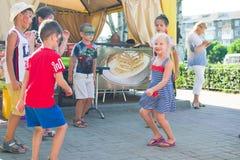Alchevsk, Ucrânia - 27 de julho de 2017: Jogo de crianças feliz com os animadores no verão Foto de Stock