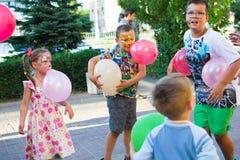 Alchevsk, Ucrania - 3 de agosto de 2017: Juegos del ` s de los niños corridos alrededor Foto de archivo