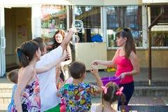 Alchevsk, Ucrania - 3 de agosto de 2017: Partido del ` s de los niños, burbujas de jabón de la captura foto de archivo