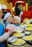 Alchevsk, Ucrania - 21 de enero de 2018: Los niños bajo la forma de cocineros aprenden cómo cocinar las lasañas imagenes de archivo