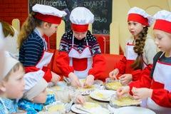 Alchevsk, Ucrania - 21 de enero de 2018: Los niños bajo la forma de cocineros aprenden cómo cocinar las lasañas fotografía de archivo