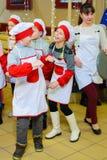 Alchevsk, Ucrania - 21 de enero de 2018: Los niños bajo la forma de cocineros están jugando y están bailando imagenes de archivo