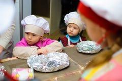 Alchevsk Ukraina - Januari 21, 2018: Barn i form av kockar lär hur man lagar mat lasagner Arkivbild