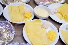 Alchevsk Ukraina - Januari 21, 2018: Barn i form av kockar lär hur man lagar mat lasagner Royaltyfri Foto