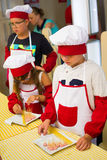 Alchevsk Ukraina - Juli 30, 2017: Skolakockar för barn Lär att laga mat pasta med korvar Royaltyfri Bild