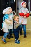 Alchevsk Ukraina, Styczeń, - 21, 2018: Dzieci w postaci kucharzów bawić się i tanczą Fotografia Royalty Free