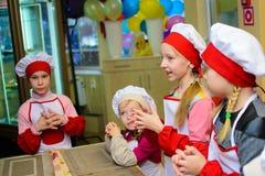 Alchevsk Ukraina, Styczeń, - 21, 2018: Dzieci w postaci kucharzów uczą się dlaczego gotować lasagna Obrazy Royalty Free