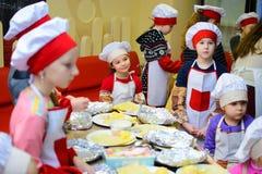 Alchevsk Ukraina, Styczeń, - 21, 2018: Dzieci w postaci kucharzów uczą się dlaczego gotować lasagna Obraz Stock