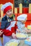 Alchevsk Ukraina, Styczeń, - 21, 2018: Dzieci w postaci kucharzów uczą się dlaczego gotować lasagna Obrazy Stock