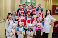 Alchevsk Ukraina, Styczeń, - 21, 2018: dzieci w postaci kucharzów pozuje z nauczycielami Obraz Stock