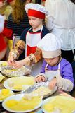 Alchevsk, Ukraine - 21. Januar 2018: Kinder in Form von Köchen lernen, wie man Lasagne kocht Lizenzfreies Stockfoto