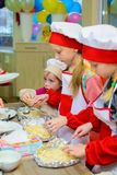 Alchevsk, Ukraine - January 21, 2018: Children in the form of cooks learn how to cook lasagna.  royalty free stock image
